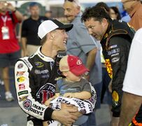 Sprint Cup Series driver Kevin Harvick (4) holds his 2-year-old son Keelan as he talks with fellow driver Tony Stewart after winning the pole for Sunday's Oral B USA 500 NASCAR auto race at Atlanta Motor Speedway Friday, Aug. 29, 2014, in Hampton, Ga. (AP Photo/John Bazemore)