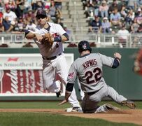 Minnesota Twins second baseman Brian Dozier (2) throws to first to complete the double play after forcing out Cleveland Indians' Jason Kipnis (22) during the fourth inning of a baseball game Sunday, Sept. 21, 2014, in Minneapolis. AP Photo/Paul Battaglia)