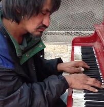 A man plays a piano in this still image taken from a video Roslyn Polard shot on her cellphone in Edmonton and posted it on YouTube, where it has since garnered nearly two million hits. Polard says she was amazed last week by the dishevelled man's music, while others who stood by listening were brought to tears. THE CANADIAN PRESS/ho-Roslyn Polard-YouTube