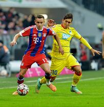 Bayern's Rafinha, left, and Hoffenheim's Roberto Firmino from Brazil challenge for the ball during the Bundesliga soccer match between FC Bayern Munich and 1899 Hoffenheim in the Allianz Arena in Munich, Germany, on Saturday, Nov. 22, 2014. (AP Photo/Kerstin Joensson)