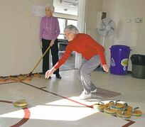 Tillie delivers a rock while Audrey looks on at the Victoria Over-50 Club's weekly game of floor curling at Victoria Community Centre.