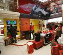 People look at clothing in a Ferrari Store in Milan, Italy, Tuesday, Dec. 9, 2014. Ferrari's sleek sports cars and souped-up Formula 1 racing machines have made the prancing horse logo among the world's most powerful brands, and now the company is preparing for a public company listing and wants to cash in on its brand recognition as a luxury goods company. (AP Photo/Luca Bruno)