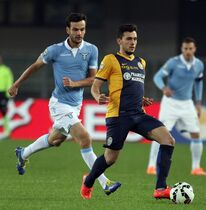 Hellas Verona's Gustavo Campanharo, right, is challenged by Lazio's Marco Parolo during a Serie A soccer match at Bentegodi stadium in Verona, Italy, Thursday, Oct. 30, 2014. (AP Photo/Felice Calabro')