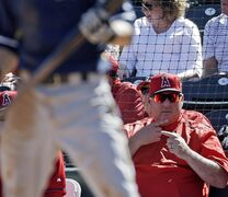 Los Angeles Angels manager Mike Scioscia sends signals as Milwaukee Brewers' Scooter Gennett bats during the third inning of a spring training baseball game Thursday, March 5, 2015, in Tempe, Ariz. (AP Photo/Morry Gash)