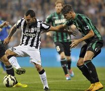 Sassuolo's Luca Antei, right, vies for the ball with Juventus' Carlos Tevez, during their Serie A soccer match at Reggio Emilia's Mapei stadium, Italy, Saturday, Oct. 18, 2014. (AP Photo/Marco Vasini)