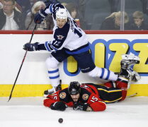 Winnipeg Jets' Olli Jokinen takes a second-period tripping penalty on Calgary Flames' Kevin Westgarth during Friday's game in Calgary.