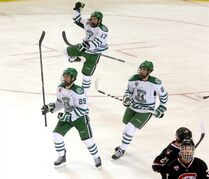 North Dakota players Bryn Chyzyk, (29), Colten St. Clair, (17), and Jordan Schmaltz (24) celebrate a goal against St. Cloud State during the first period of NCAA west regional championship hockey game, Saturday, March 28, 2015 in Fargo, N.D. (AP Photo/Bruce Crummy)