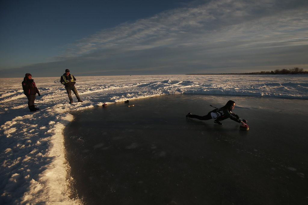 Kerri Einarson curls on her homemade rink on Lake Winnipeg north of Gimli as her parents Jeff and Marilyn Flett look on. Her father made the rink so Einarson could practise for the upcoming Scotties Tournament of Hearts in Calgary. (John Woods / Winnipeg Free Press)