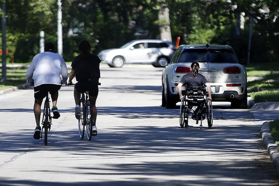 A person in a wheelchair makes their way down Wellington Crescent alongside two cyclists earlier this month. (John Woods / Winnipeg Free press files)