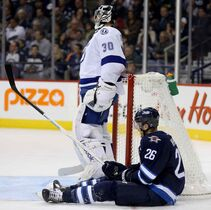 Winnipeg Jets' Blake Wheeler (26) sits on the ice next to Tampa Bay Lightning goaltender Ben Bishop (30) during second period of Friday's game at the MTS Centre.