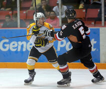 Wheat Kings' Jayce Hawryluk reacts to a cross-check from Calgary Hitmen's Keegan Kanzig Saturday in Brandon.