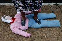 A demonstrator steps on an effigy of Brazilian President Dilma Rousseff during a protest march demanding the impeachment of the newly re-elected leader, over an alleged scheme of corruption that siphoned money from the state-owned oil company Petrobras, in Brasilia, Brazil, Saturday, Nov. 15, 2014.