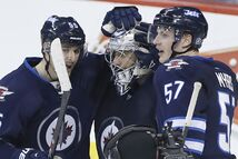 The Jets congratulate Ondrej Pavelec after the puckstopper earned a shutout against the Capitals.