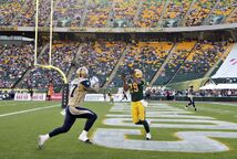 Bombers receiver Rory Kohlert (left) tries to stop the interception by Edmonton's Chris Thompson Saturday in Edmonton.