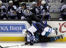 Jets defenseman Jacob Trouba levels Sharks centre Logan Couture.