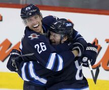 Winnipeg Jets' Blake Wheeler (26) and Jacob Trouba (8) celebrate after Trouba scored the game-winning goal in overtime to beat the Edmonton Oilers at MTS Centre in Winnipeg Saturday afternoon.