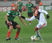 Douglas Costa, right, of FC Shakhtar Donetsk duels for the ball with Mikel Rico of Athletic Bilbao during the Champions League Group H soccer match between Athletic Bilbao and FC Shakhtar Donetsk in Lviv, Western Ukraine, Tuesday, Nov. 25, 2014. (AP Photo/Pavlo Palamarchuk)