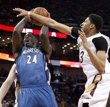 New Orleans Pelicans forward Anthony Davis (23) fouls Minnesota Timberwolves forward Anthony Bennett (24) during the first half of an NBA basketball game in New Orleans, Sunday, March 29, 2015. (AP Photo/Scott Threlkeld)