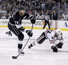 Los Angeles Kings center Jeff Carter, left, shoots past Chicago Blackhawks defenseman Johnny Oduya during the second period of Game 4 of the Western Conference finals of the NHL hockey Stanley Cup playoffs in Los Angeles, Monday, May 26, 2014. THE CANADIAN PRESS/AP/Chris Carlson