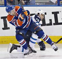 Winnipeg Jets Patrice Cormier (28) is checked by Edmonton Oilers Mitchell Moroz (53) during second period NHL hockey action in Edmonton, on Monday September 29, 2014. THE CANADIAN PRESS/Jason Franson