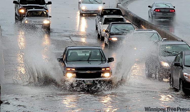 Vehicles try to make it through deep water Saturday evening under the Jubilee Underpass on Pembina Highway.