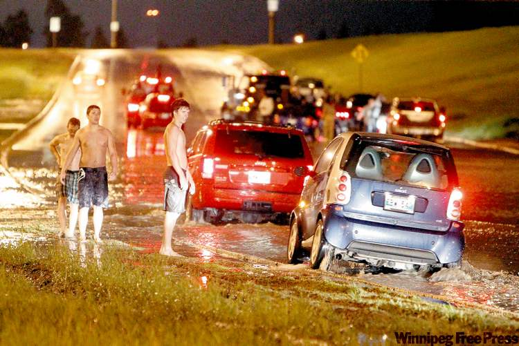 At 2 a.m. Sunday, Taylor McIntyre, 18, Jared Hancox, 21, and Riley Smith, 20, assist passing motorists on Bishop Grandin Boulevard at the Pembina Highway underpass.