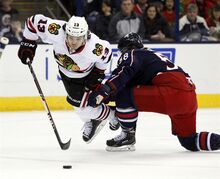 Chicago Blackhawks' Daniel Carcillo, left, works for the puck against Columbus Blue Jackets' David Savard during the first period of an NHL hockey game in Columbus, Ohio, Saturday, Dec. 20, 2014. (AP Photo/Paul Vernon)