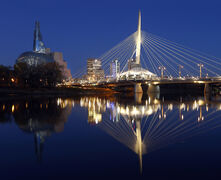 Esplanade Riel reflects on the Red River  before dawn with the Canadian Museum for Human Rights in the background.