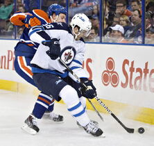 Winnipeg Jets Adam Lowry (56) and Edmonton Oilers Nikita Nikitin (86) battle for the puck during first period NHL hockey action in Edmonton Monday.