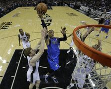 Dallas Mavericks' Monta Ellis (11) drives to the basket between San Antonio Spurs' Matt Bonner, left, and Tim Duncan, right, during the first quarter of Game 1 of the opening-round NBA basketball playoff series, Sunday, April 20, 2014, in San Antonio. (AP Photo/Eric Gay)