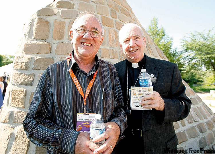 Piet Meiring of South Africa, left, and Alberta archbishop Gerard Pettipas at a Wednesday morning pipe ceremony at The Forks, part of the Truth and Reconciliation commission. Thousands of residential school survivors are expected to attend.