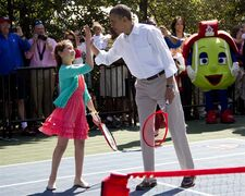 FILE - In this April 9, 2012 file photo, President Barack Obama high-fives his tennis partner, 9-year-old Isabella Irlando of Los Angeles during the annual White House Easter Egg Roll, at the White House in Washington. Obama's summer fashion choice, not unprecedented among presidents - himself included - was the talk of social media, Thursday, Aug. 28, 2014. Other presidents who have taken on tan include Bill Clinton, Ronald Reagan, George H. W. Bush, George W. Bush and Dwight Eisenhower. (AP Photo/Carolyn Kaster, file)