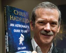 Canadian astronaut Chris Hadfield holds a copy of his book