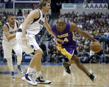 Dallas Mavericks' Dirk Nowitzki (41) of Germany defends as Los Angeles Lakers guard Kobe Bryant (24) finds room to the basket for a shot in the first half of an NBA basketball game, Friday, Nov. 21, 2014, in Dallas. The Mavericks' Chandler Parsons watches from behind. (AP Photo/Tony Gutierrez)