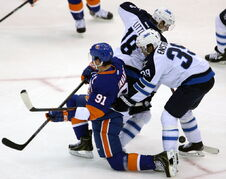 Winnipeg Jets' Bryan Little (18) and Tobias Enstrom (39) tangle with New York Islanders' John Tavares (91) during first period NHL hockey action at Nassau Coliseum, Uniondale, N.Y. Tuesday.
