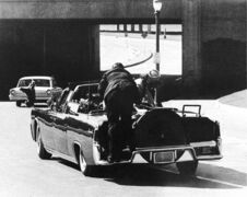 After being fatally shot, president Kennedy slumps down in the back seat of the presidential limousine as it speeds along Elm Street toward the Stemmons Freeway overpass  in Dallas. First lady Jacqueline Kennedy leans over the president as Secret Service agent Clint Hill pushes her back to her seat.  'She's going to go flying off the back of the car,' Hill thought as he tried to secure the first lady.