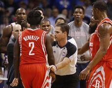 Official David Guthrie, center, holds back Houston Rockets guard Pat Beverley (2) from Oklahoma City Thunder guard Russell Westbrook, between Guthrie and Beverley, during the first quarter of an NBA basketball game in Oklahoma City, Tuesday, March 11, 2014. (AP Photo/Sue Ogrocki)