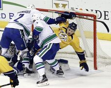 Nashville Predators left wing Taylor Beck (41) is checked into the net by Vancouver Canucks defenseman Dan Hamhuis (2) in the second period of an NHL hockey game Tuesday, March 31, 2015, in Nashville, Tenn. (AP Photo/Mark Humphrey)