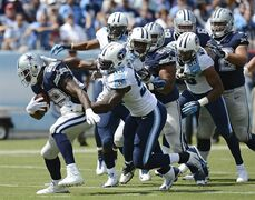 Dallas Cowboys running back DeMarco Murray (29) is chased by Tennessee Titans defenders, including Kamerion Wimbley (95), in the second quarter of an NFL football game Sunday, Sept. 14, 2014, in Nashville, Tenn. Murray rushed for 167 yards and scored one touchdown as the Cowboys won 26-10. (AP Photo/Mark Zaleski)