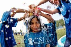 "Harmony, 7, from the Westgrove School Investigators Summer Learning Program gets ""sponged"" during a water fight at the Waverley Soccer Complex for the first Jumpstart Games on July 31. The Westgrove Community School's literacy camp is partially funded by a donation from the Rotary Club of Winnipeg-Charleswood."