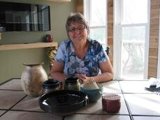 Oak Bluff resident Deb Brown shown with some of the functional pottery pieces she has created at her home.