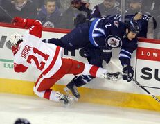 The Jets' Adam Pardy gets by Redwings' Tomas Tatar during the first period of Thursday's game at the MTS Centre.