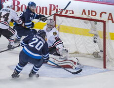 Winnipeg Jets' Lee Stempniak (20) takes a shot on Chicago Blackhawks' Corey Crawford (50).