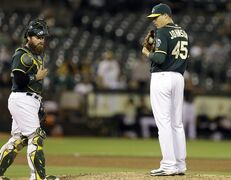 In this photo from Monday, May 12, 2014, Oakland Athletics pitcher Jim Johnson, right, waits to speak with catcher Derek Norris during a baseball game against the Chicago White Sox in Oakland, Calif. Johnson was released by the Athletics on Thursday, July 24, 2014. (AP Photo/Ben Margot)