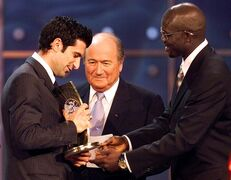FILE - In this Monday, Dec. 17, 2001 file photo, Portuguese player Luis Figo, left, of Spanish team Real Madrid receives his trophy as FIFA