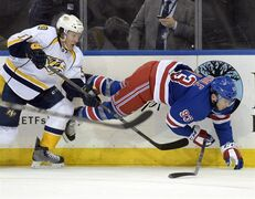 New York Rangers' Keith Yandle (93) is tripped up by Nashville Predators' Gabriel Bourque during the second period of an NHL hockey game Monday, March. 2, 2015, at Madison Square Garden in New York. (AP Photo/Bill Kostroun)