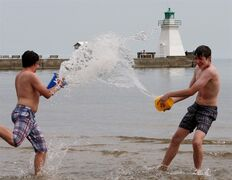 Kyle Lynch (left) and friend Alex Durocher splash each other as they enjoy the mild weather on the beach, Saturday, May 18, 2013 in Port Dover, Ont. Get ready to break out the sunscreen Canada, but don't worry about sizzling all season.Meteorologists at AccuWeather.com say the majority of Canadians can look forward to a more
