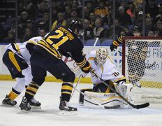 Buffalo Sabres right winger Drew Stafford (21) pushes the puck past Nashville Predators goaltender Carter Hutton (30) for a goal during the first period of an NHL hockey game, Tuesday, March 11, 2014, in Buffalo, N.Y. (AP Photo/Gary Wiepert)