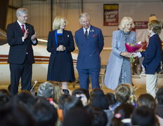 Prince Charles looks on as Camilla accepts a bouquet of flowers.