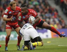 Toulon's Mathieu Bastareaud, centre, is tackled by Clermont Auvergne's Wesley Fofana as Toulon's Jonny Wilkinson looks on during their European Rugby Union Cup final at the Aviva Stadium, Dublin, Ireland, Saturday, May 18, 2013. (AP Photo/Peter Morrison)